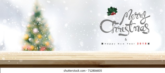 Wood table top with a blurred Christmas tree and snow falling in panoramic banner  background - can be used for display or montage your products