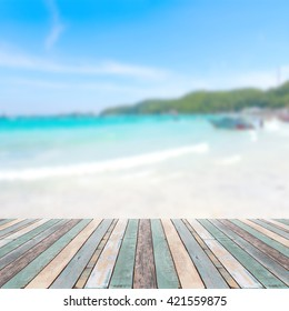 Wood table top with blurred nature scene tropical beach and blue sky, holiday background concept - can be used for display or montage your products