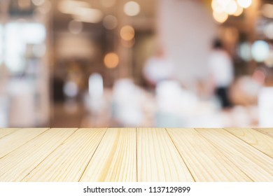wood table top with cafe restaurant with abstract bokeh lights defocused blur background for product display