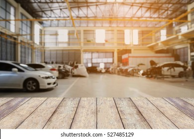 Wood table top with Car repair service centre interior blurred background. For create montage auto product display.