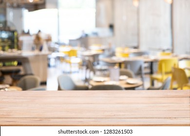 Wood table top with defocused background of restaurant, bar or cafeteria background for your product display.