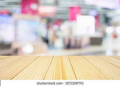 wood table top with eletronic department store show Television TV and home appliance with bokeh light blurred background
