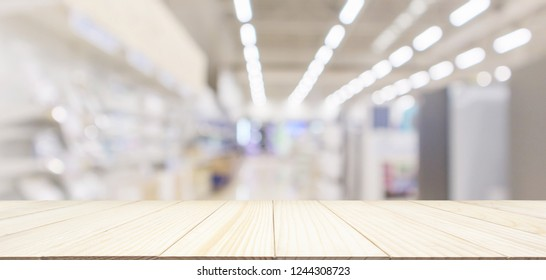 wood table top with eletronic department store in supermarket shopping mall show Television TV refrigerator and home appliance with bokeh light blurred background for product display