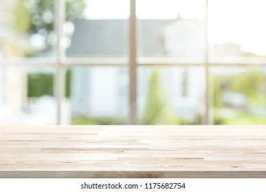 Wood table top inside the house with sunlight shining through window and blur green garden as background, can be used for display and montage your products or food