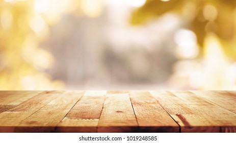 Wood table top on blur abstract natural foliage bokeh background, vintage tone - can be used for display or montage your products