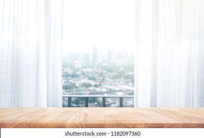 Wood table top on on blur of curtain with window city view background.For create product display or design key visual layout
