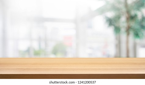 Wood table top on blur white glass wall background form office building.For montage product display and design key visual layout