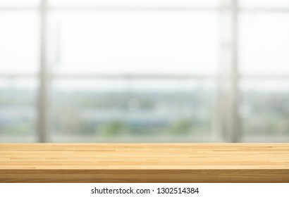 Wood table top on blur window glass, restaurant wall background.For montage product display or design key visual layout background.