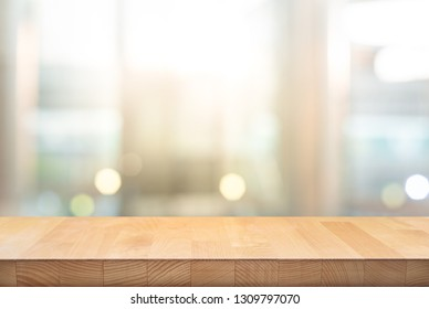 Wood table top on blur window glass,wall background.For montage product display or design key visual layout background. - Image