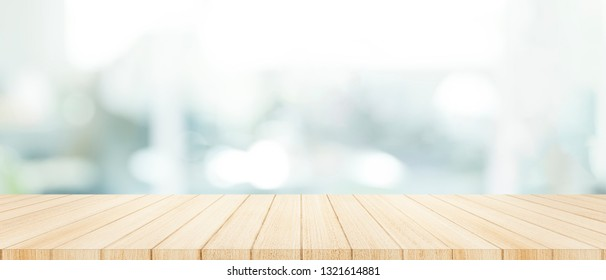 Wood table top on  with blur glass window wall background.