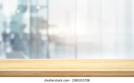 Wood table top on blur window glass,wall background with city view.For montage product display or design key visual layout