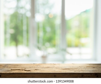 Wood table top on blur of window glass and abstract green from garden with city view in the morning background. For montage product display