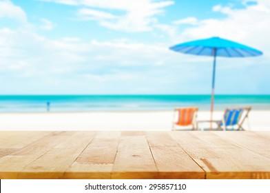 Wood table top on blur beach background with beach chairs and parasol - can be used for display or montage your products