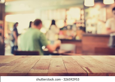 Wood table top on blur background of coffee shop interior with some people, vintage tone - can be used for display or montage your products