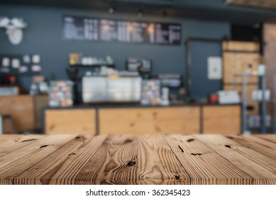 Wood table top on blur coffee shop background