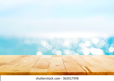 Wood table top on blur summer blue sea and sky background - can be used for display or montage your products