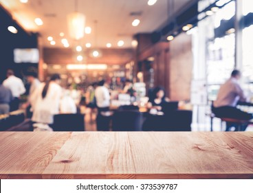 Wood  table top on blur of people in coffee shop or restaurant with bokeh background.For montage product display