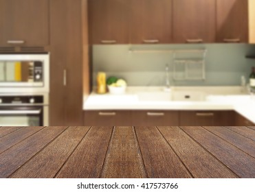 Wood table top on blur the background of the kitchen. - can be used for display your products or promotional and advertising posters