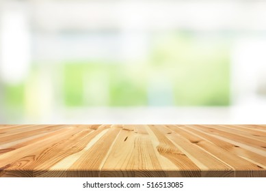 Wood table top on blur white green background from kitchen window - can be used for display or montage your products (or foods)