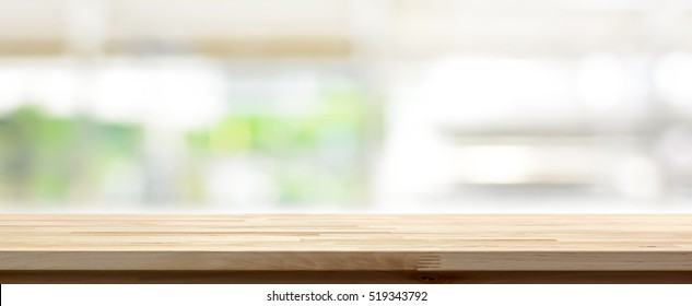 Wood table top on blur kitchen window background, panoramic banner - can be used for display or montage your products (or foods)