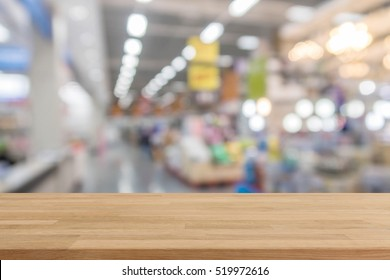 Wood table top on blur with bokeh shopping mall background - can be used for display or montage your products