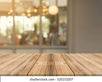 Wood table top on blur kitchen in home background. Perspective brown wooden table over blur in kitchen loft background - can be used mock up for montage products display or design key visual layout.