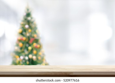Wood table top on blur Christmas tree background - can be used for montage or display your products