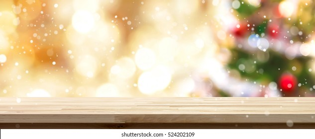 Wood table top on  blur colorful Christmas tree and gold bokeh background with snowfall