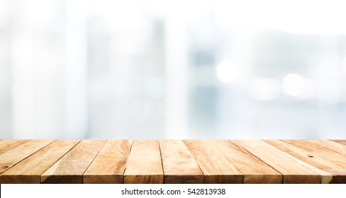 Wood table top on blur glass window wall building background.For montage product display or design key visual layout background.
