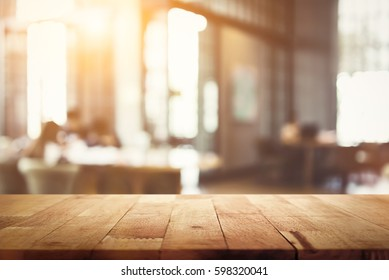 Wood table top on blur restaurant (cafe) interior background - can be used for display your products or foods