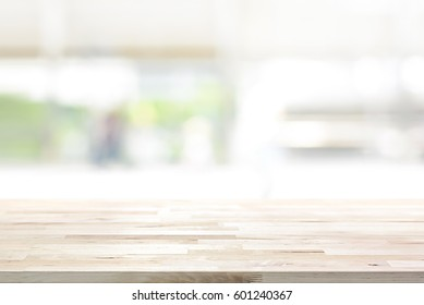 Wood table top on blur white green kitchen window background - can be used for display or montage your products (foods)