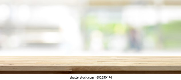 Wood table top on blur white green kitchen window background, panoramic banner - can be used for display or montage your products (foods)