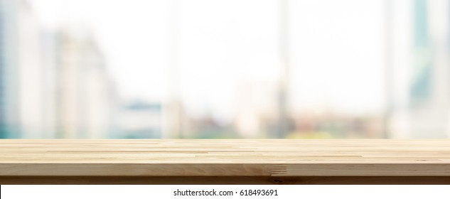 Wood table top on blur  city building view background looking through glass window, panoramic banner - can be used for display or montage your products