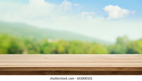 Wood table top on blur tree and mountain background .summer,nature concepts
