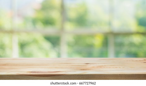 Wood table top on blur of window glass and abstract green from garden background.