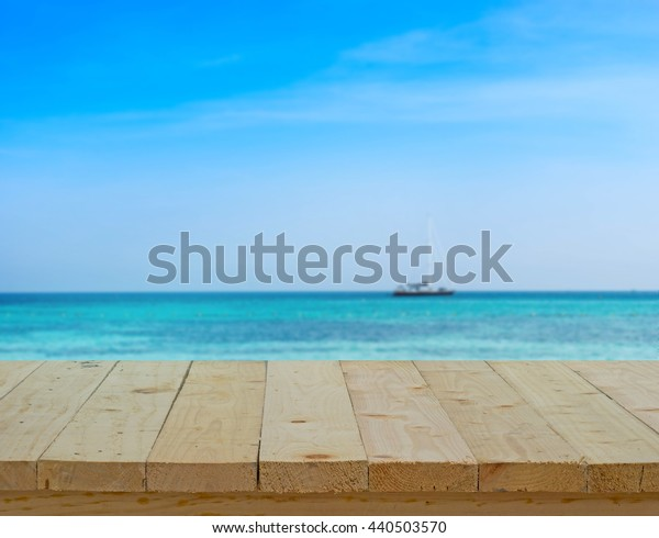 wood table top on blur background of seascape view  - can use to display or montage on product