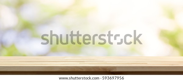Wood table top on blur white green natural abstract background from tree branches - panoramic banner