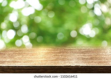 Wood table top on blurred green background with beautiful green bokeh of natural tree. Summer. Nature. Copy space. Double exposure. Can be use for display, montage, brochure or advertising.
