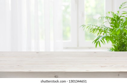 Wood table top on blurred background of window with curtain