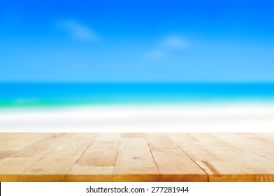 Wood table top on blurred beach background, summer concept  - can be used for display or montage your products