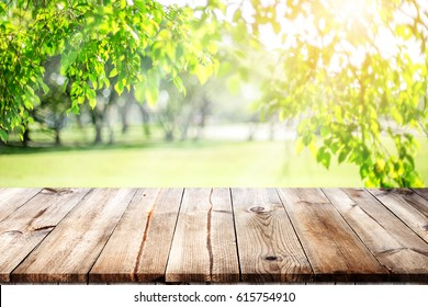 Wood table top on blurred lawn  green background for montage or display your products