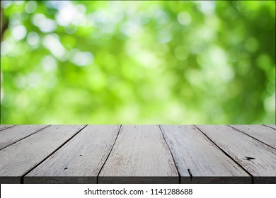 Wood table top on bokeh abstract green background.  display your products. work space