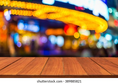 Wood table top on bokeh marquee light of theatre background. can be used for display or montage your products