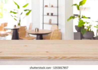 Wood table top on defocused restaurant or coffee shop background