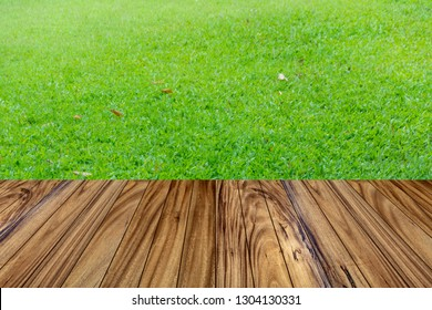 Wood table top on green grass in garden background. Can used for display or montage your product.