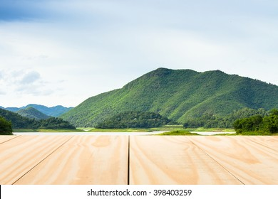 Wood table top on lake and tropical forest mountain background. can used for display or montage your products