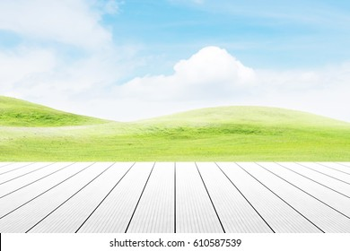 Wood table top on mound slope green grass natural background. concept party,display, county, products,natural,farm,organic.