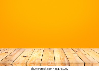 Wood table top on orange wall background
