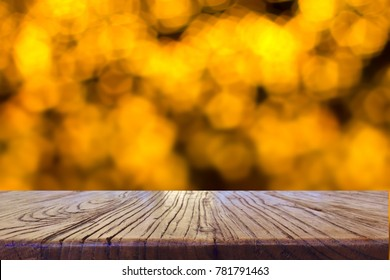 Wood table top on shiny bokeh gold background - can be used for display or montage your products