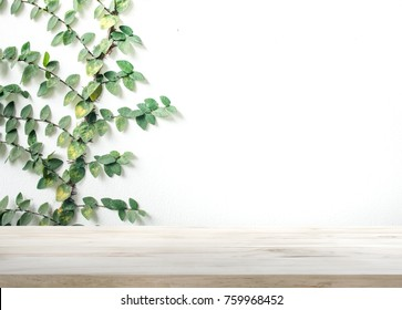 Wood table top on white wall with leaf background.For montage product display or design key visual layout